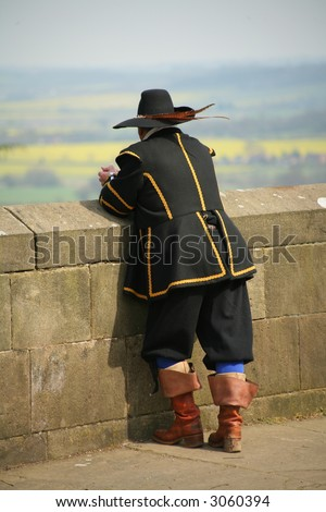 man in period costume looking over wall - stock photo