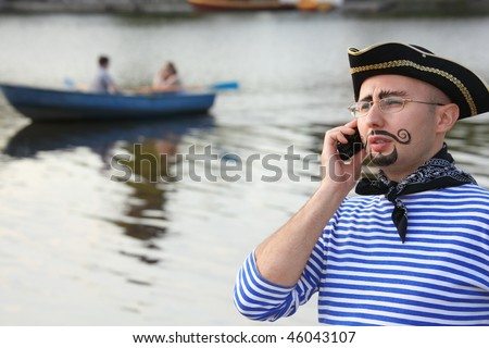 man in pirate suit is talking by the phone. boat in out of focus - stock photo