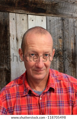 Man in plaid shirt with rustic background. - stock photo