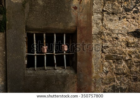 Man in prison and behind grate - stock photo