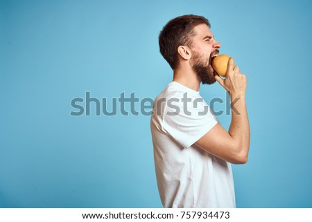 man in profile eating an orange on a blue background, citrus, fruit