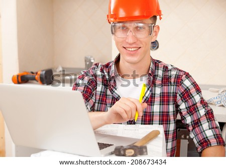 man in protective helmet sits near laptop. repairer receives education in the workplace online - stock photo