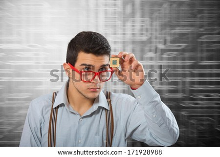 Man in red-framed glasses looking at the microprocessor in his hand - stock photo