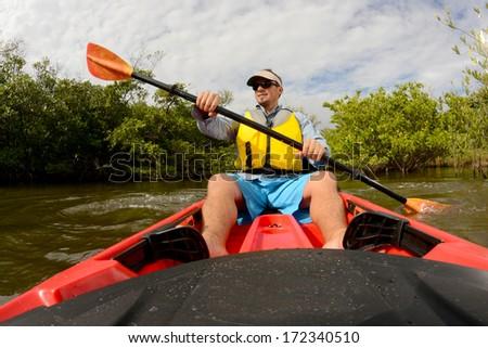 man in red kayak in florida - stock photo