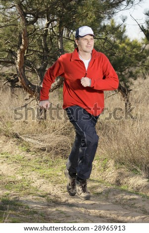 Man in red shirt while out jogging - stock photo