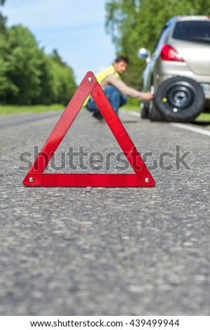 Man in reflective vest changing the tire after car breakdown. Focus on red triangle emergency sign. - stock photo