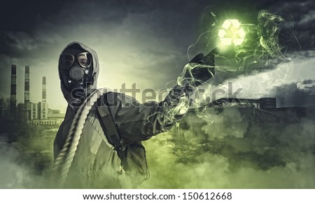 Man in respirator against nuclear background touching symbol. Recycle concept