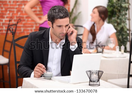 Man in restaurant with computer and phone