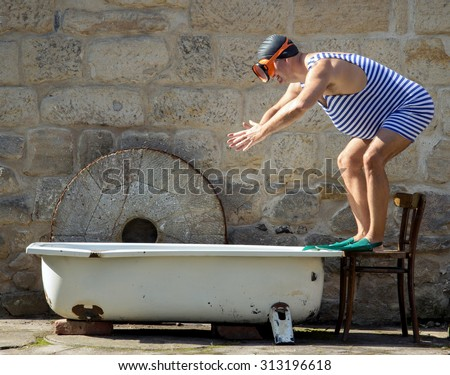 man in retro swimsuit jumps to the outdoor bathtub. Funny fat swimmer in retro style jumps into the tub. Vintage style swimwear man starting swim in bathtub.Man with snorkel train jump into the water. - stock photo