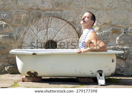 man in retro swimsuit resting in the outdoor bathtub.Man relaxes in the old bathtub outside.Vintage style man use outdoor bath. Bath in the outdoor tub.Man in retro swimsuit sunbathing in the bathtub. - stock photo