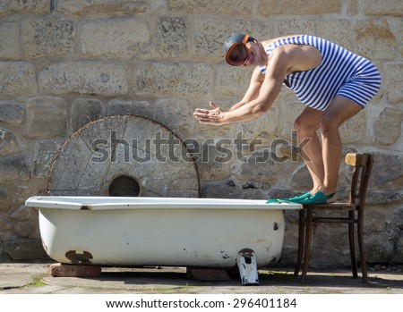 Man in retro swimsuit want jumps to the outdoor bathtub. Funny man in retro swimwear starts to swim in bathtub. Diver in retro style swimsuit with diving goggles and bathing cap. Snorkel in bathtub. - stock photo