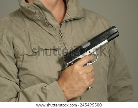 Man in rumpled jacket points a gun - stock photo
