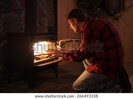 man in rustic setting warming hands by wood stove