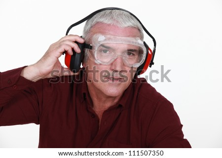 Man in safety goggles and ear defenders - stock photo