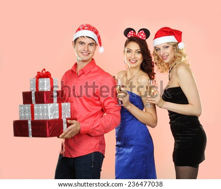 man in santa hat gives a lot of bright gifts for Santa girls - stock photo