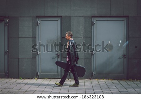 Man in short sleeve shirt walking in the street with guitar case - stock photo