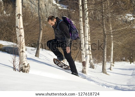 Man in snow shoes in a winter forest - stock photo