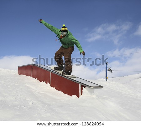 Man in snowboard park on slide-box for snowboarding in mountains - stock photo
