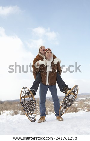 Man in snowshoes giving woman piggyback ride - stock photo