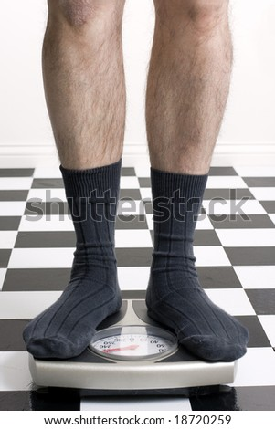 Man in socks standing on scale with on checkered floor that is slightly burned out in background - stock photo
