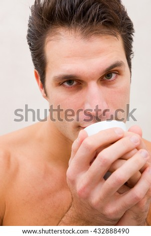 Man in spa holding cup near mouth - stock photo