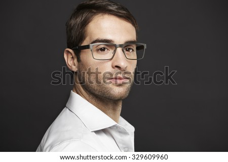 Man in spectacles looking away, studio - stock photo