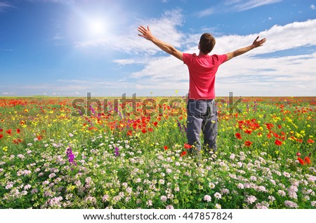 Man in spring meadow of flower. Emotional scene. - stock photo