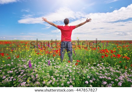 Man in spring meadow of flower. Emotional scene.