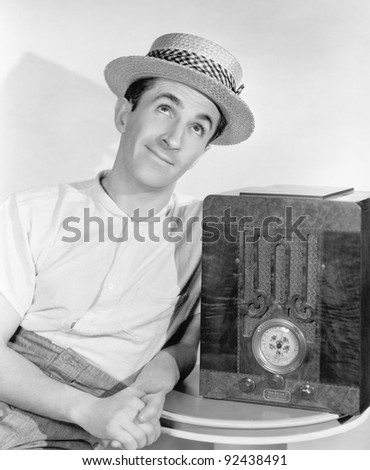 Man in straw hat listening to the radio - stock photo