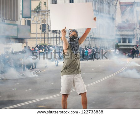 man in street protest with blank cardboard, looks great for advertistment with attitude - stock photo