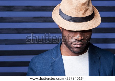 Man in style. Handsome young African man in hat standing against striped background - stock photo