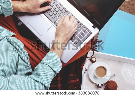 Man in stylish casual clothes with a laptop on his lap typing on the keyboard and drinking morning coffee with sweets. The concept of personal productivity and work remotely - stock photo