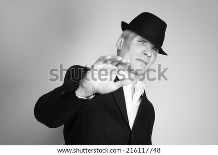 Man in suit and black hat at the age of forty-six years old  looking at the camera on the background of a rough wall with texture - stock photo