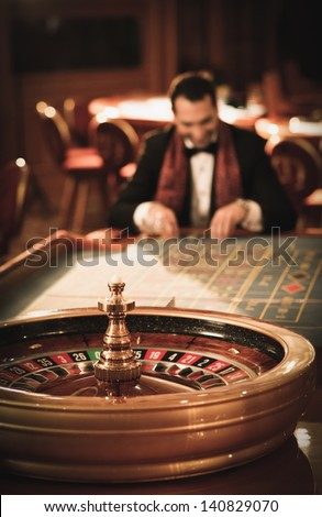 Man in suit and scarf playing roulette in a casino - stock photo