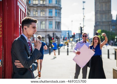 Man in suit and tie against a background of London Big Ben standing near the phone and listening to music with headphones in the background a group of people with tables where you can place a label