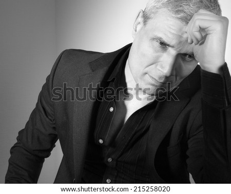 Man in suit at the age of forty-six years old  with hand to head support  looking down on the background of a rough wall with texture - stock photo