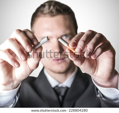 Man in suit breaking the cigarette