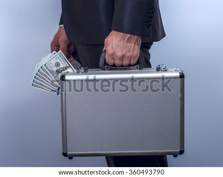 Man in suit carries metal briefcase with dollars - stock photo