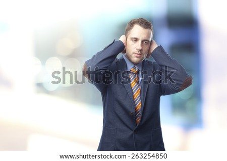 Man in suit covering his ears - stock photo