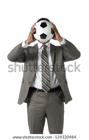 Man in suit covering his face using a soccer ball - stock photo