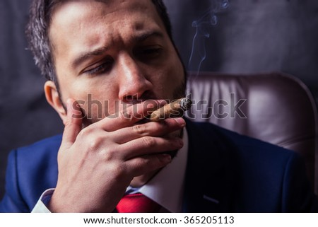 Man in suit dress smoking a cuban cigar.Black background.Black background