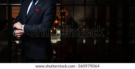 Man in suit fixing his cufflinks - stock photo