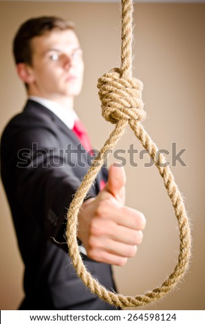 man in suit giving thumbs up with hanging noose - stock photo