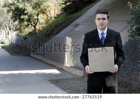 Man in suit holding a cardboard sign.