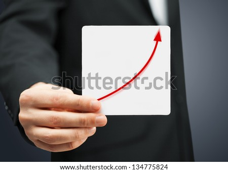 man in suit holding card with increasing graph on it - stock photo