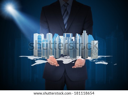 Man in suit holding city of skyscrapers in the hand. Spotlight shines skyscrapers