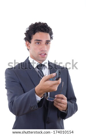 Man in suit holding glasses and changing channel with remote - stock photo