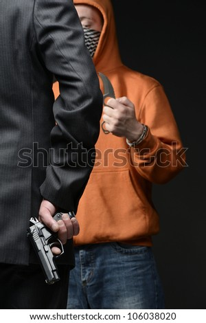 Man in suit holding gun behind his back, in front of him man with knife - stock photo