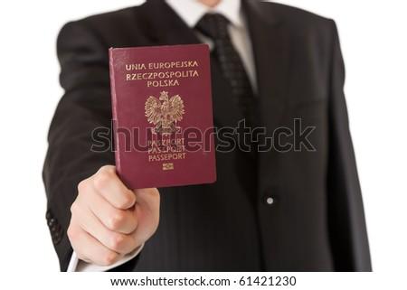 Man in suit holding passport - stock photo