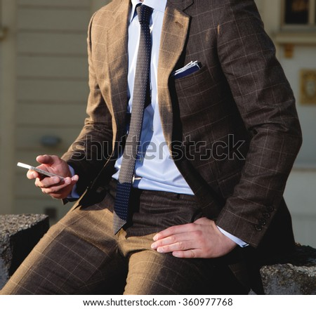 Man in suit holding phone in his hand - stock photo